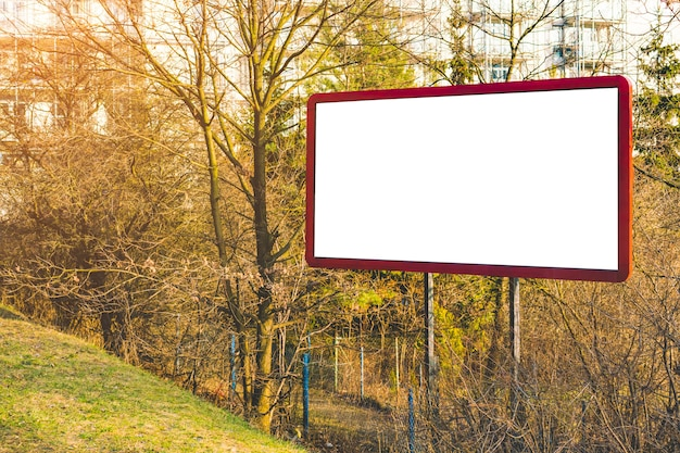 Leeg aanplakbord of groot bord met klein bos en appartementen. reclame leeg