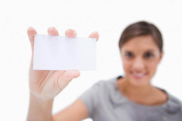 Leeg adreskaartje dat door glimlachende vrouw wordt voorgesteld