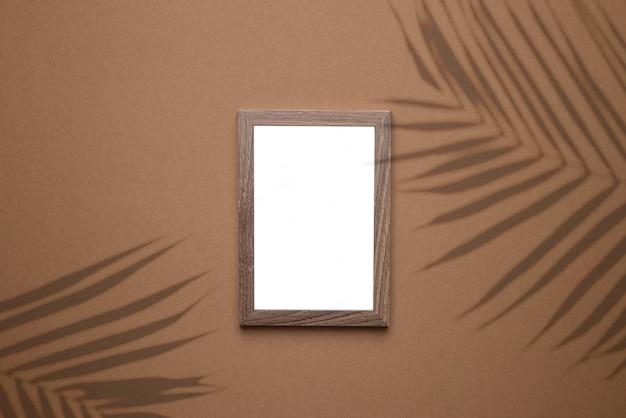 Leeg afbeeldingsframe op trend bruine achtergrond met tropisch plantenschaduwlicht als sjabloon voor evenementpromotie, ontwerppresentatie, zelfportfolio enz. bovenaanzicht