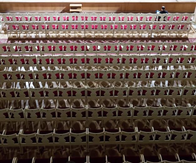Leeg auditorium in de schemering voor het concert. eenzame toeschouwer op de eerste rij. bovenaanzicht