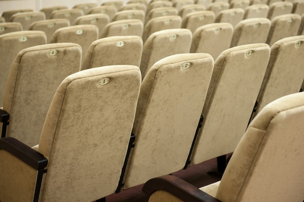 Leeg auditorium met beige stoelen, theater of conferentiezaal.