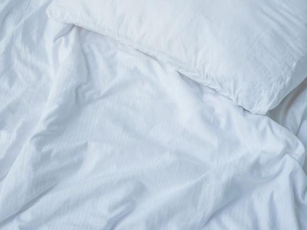 Leeg bed met verwarde kussens en lakens
