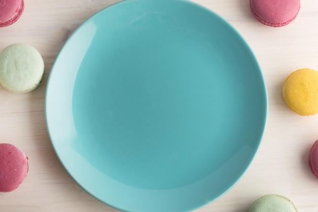 Leeg blauw helder bord, met een heerlijk rond dessert, makarons