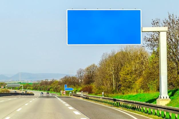 Leeg blauw snelwegteken over de weg op zonnige dag