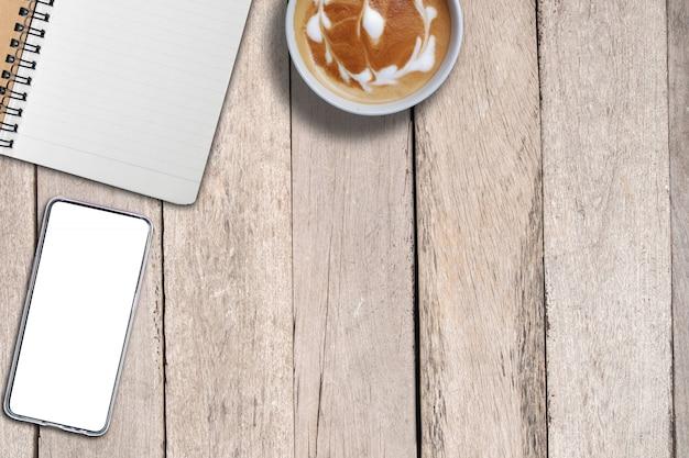 Leeg boek en bespotten omhoog slimme telefoon en koffie op bureau