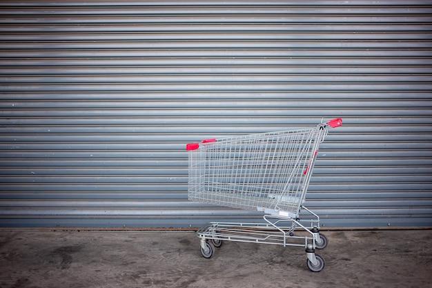 Leeg boodschappenwagentje op dichte winkeldeur