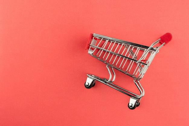 Leeg boodschappenwagentje op roze achtergrond. - voor reclame en voor kopieerruimte.