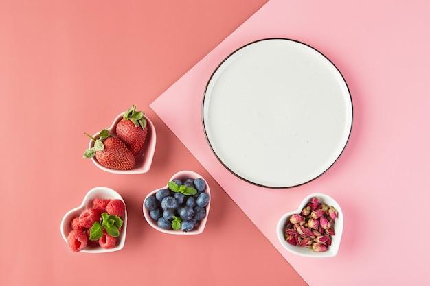 Leeg bord en kleine bordjes in de vorm van harten met verse aardbeien frambozen bosbessen