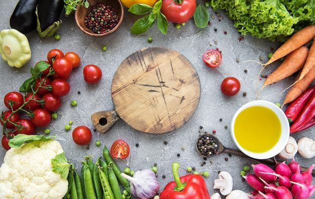 Leeg bord en verse groenten op een concrete achtergrond