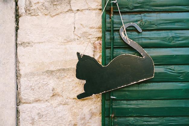 Leeg bord in de vorm van een zwarte kat die op een groene houten deur hangt