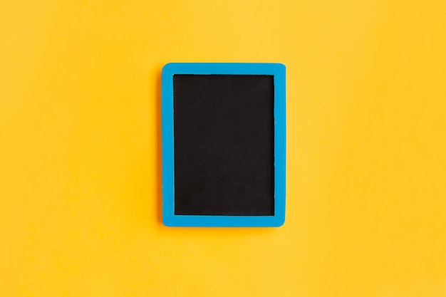 Leeg bord met blauw houten frame op geel