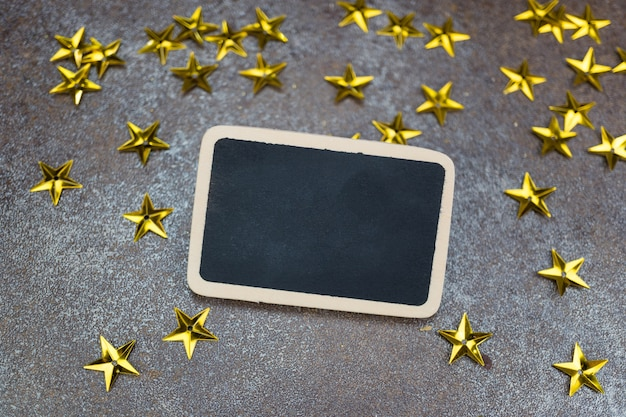 Leeg bord met gouden sterren op rustieke tegelachtergrond
