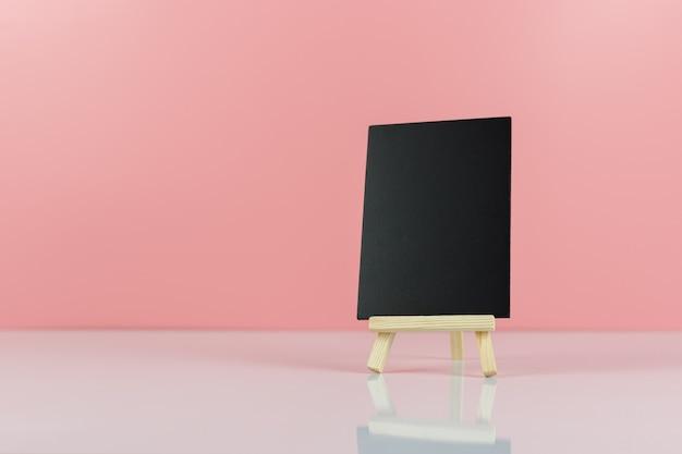 Leeg bord met statief op roze tafelachtergrond.