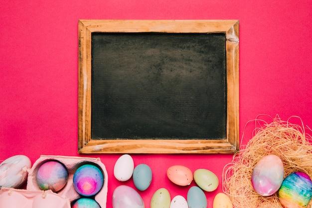 Leeg bord met veel kleurrijke paaseieren op roze achtergrond
