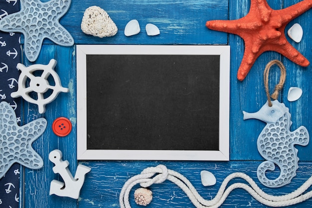 Leeg bord met zeeschelpen, stenen, touw en stervissen op blauwe houten achtergrond, exemplaar-ruimte