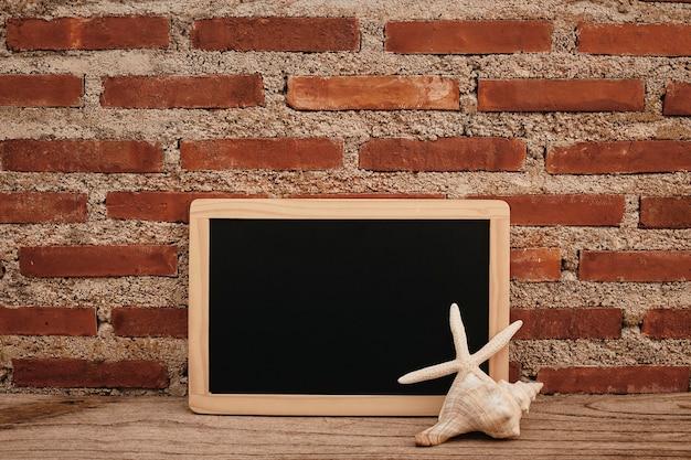 Leeg bord op houten bureau en bakstenen muur, schaaldieren en duikglazen kopiëren ruimte voor uw tekst of ontwerp. vooraanzicht