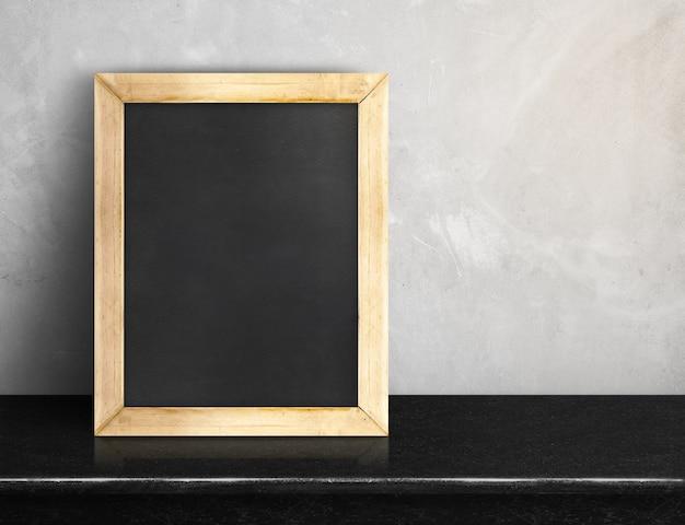 Leeg bord op zwarte marmeren lijst bij grijze concrete muur