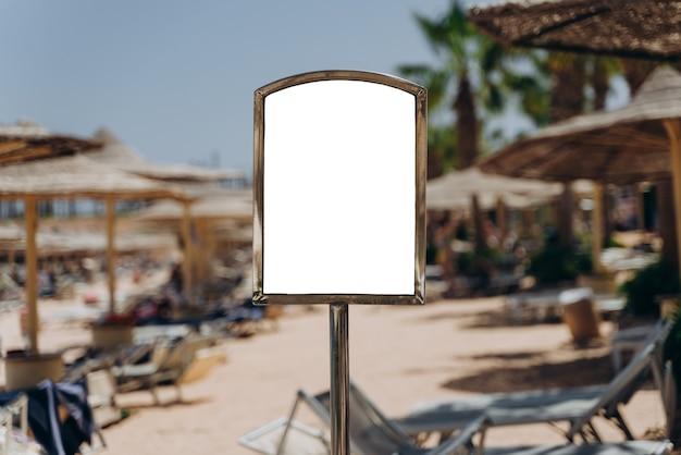 Leeg bord voor reclame op het strand bij de zee