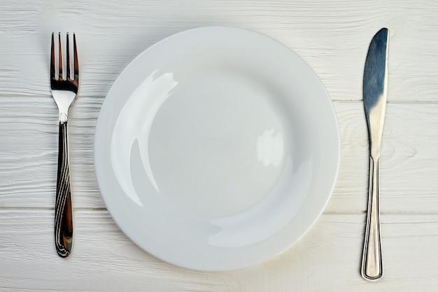 Leeg bord, vork en mes. keuken gebruiksvoorwerp op witte houten tafel, bovenaanzicht. restaurant tafel instelling.