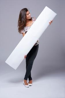 Leeg bordje vastgehouden door een jonge vrouw