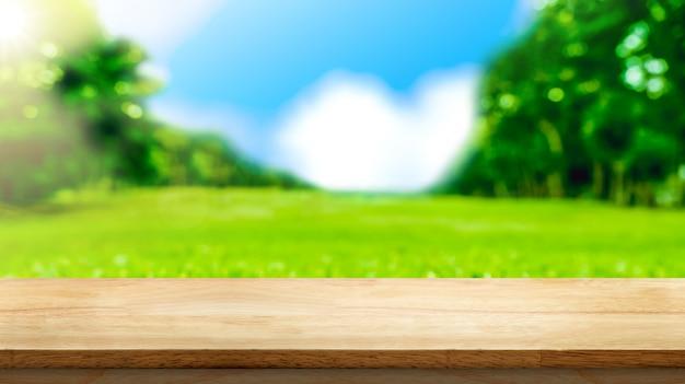 Leeg bruin houten tafelblad met wazig groene velden in het park