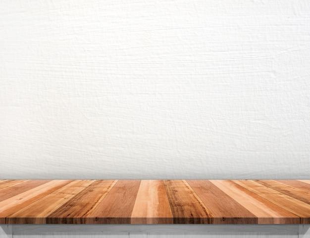 Leeg bruin houten tafelblad met witte betonnen muur