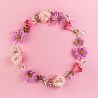 Leeg cirkelkader met bloemen op roze achtergrond wordt gemaakt die
