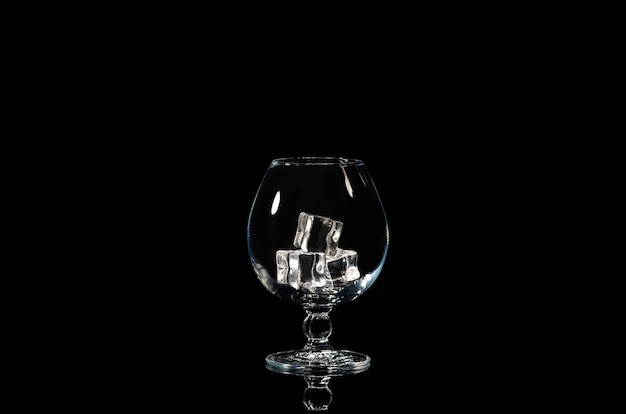 Leeg cognacglas met ijsblokjes