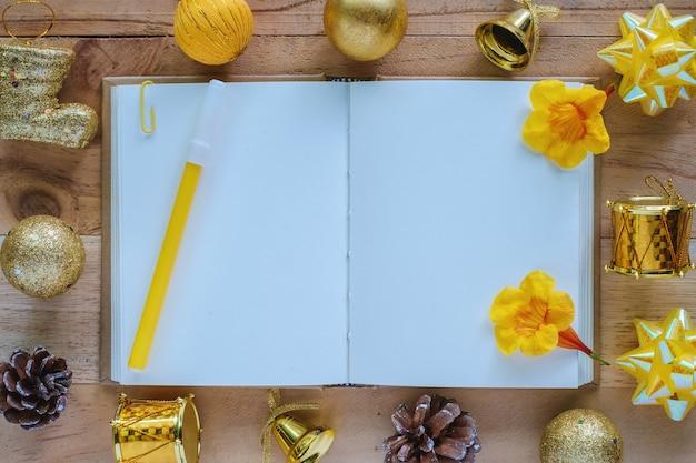 Leeg dagboeknotitieboekje met kerstmis en nieuwjaarornamenten en decoratie op houten lijst