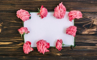 Leeg document met roze rozen over geweven houten lijst