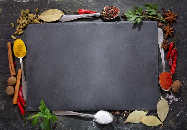 Leeg donker bord met verschillende kruiden en specerijen om te koken, bovenaanzicht