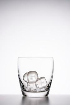 Leeg duidelijk whiskyglas met ijs op een witte achtergrond. verticale foto, kopieer ruimte.
