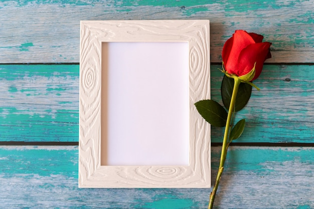 Leeg fotoframe en rode rozen over houten tafel