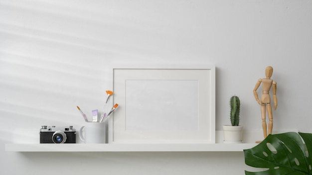 Leeg fotokader, camera en decoraties op witte plank met witte muur