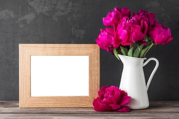 Leeg fotokader met het rode boeket van pioenbloemen op rustieke houten lijst.