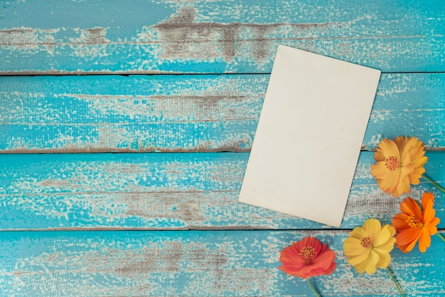 Leeg fotokaderalbum met bloem op oude blauwe houten achtergrond