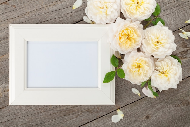 Leeg fotolijstje en witte rozen over houten tafel achtergrond