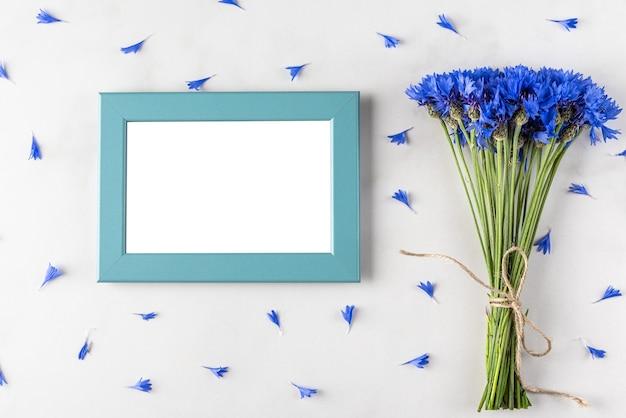 Leeg fotolijstje met zomers blauw korenbloemenboeket op wit marmeren oppervlak