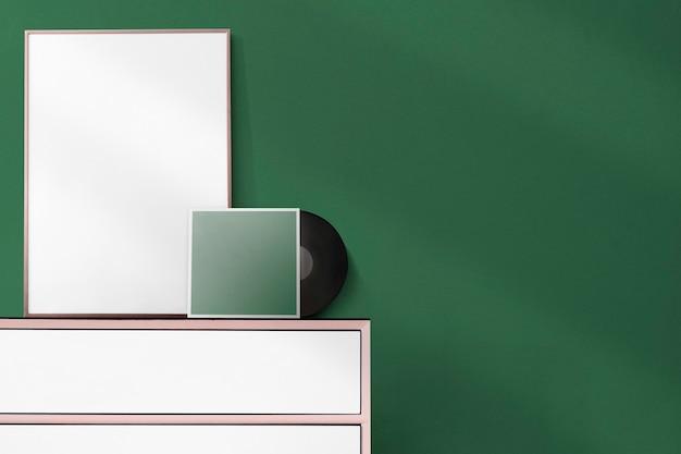 Leeg frame en vinyl tegen groene muur