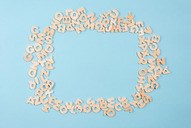 Leeg frame gemaakt met houten alfabetten op blauwe achtergrond