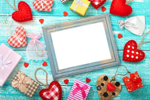 Leeg frame, geschenkdozen en harten op houten tafel.