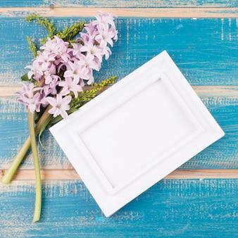 Leeg frame met bloemen op tafel