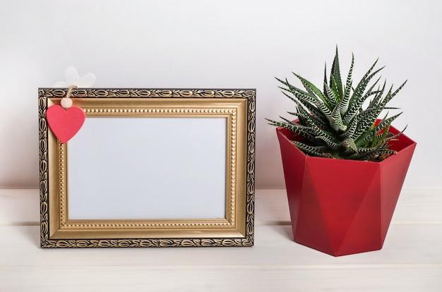 Leeg frame met hart en een cactus op een witte houten ondergrond