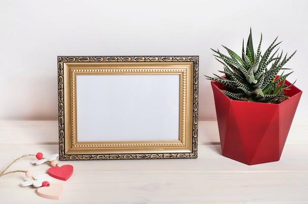 Leeg frame met hartjes en een cactus op een witte houten ondergrond