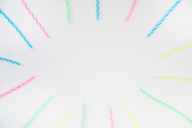 Leeg frame met kleurrijke strepenkaarsen op witte achtergrond