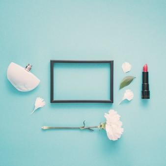 Leeg frame met lippenstift en bloem op tafel