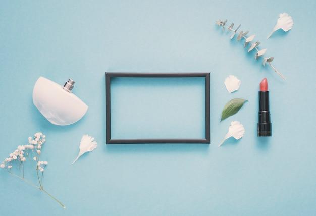Leeg frame met lippenstift en planten op tafel