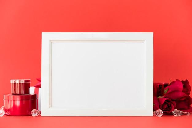 Leeg frame met rode rozen op tafel