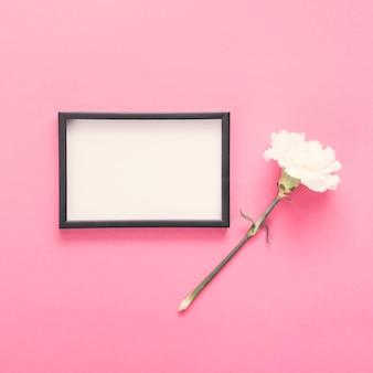 Leeg frame met witte bloem op tafel