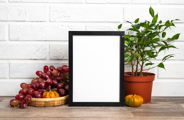 Leeg frame naast bloempot en druiven